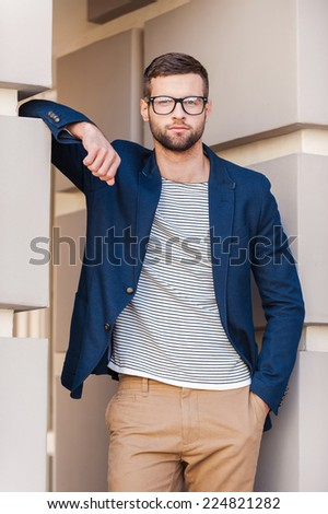 Cool and handsome. Handsome young man in smart jacket looking at camera while standing outdoors - stock photo