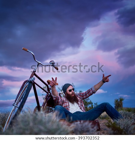cool bearded traveler making hand gesture beside bike in desert - stock photo