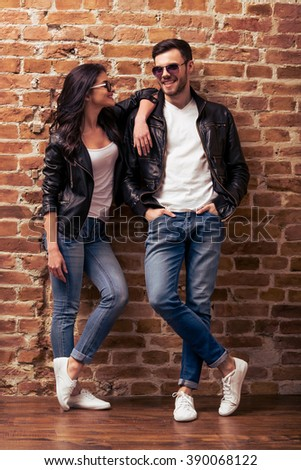 Cool beautiful young couple in leather jackets and sunglasses is looking at camera, posing and smiling, standing against brick wall - stock photo