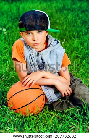 Cool boy lying on a grass with a basketball at a park. Summer day.  - stock photo
