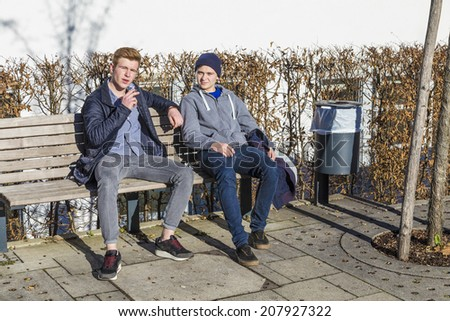 cool boys sitting on a bench with a cigarette - stock photo
