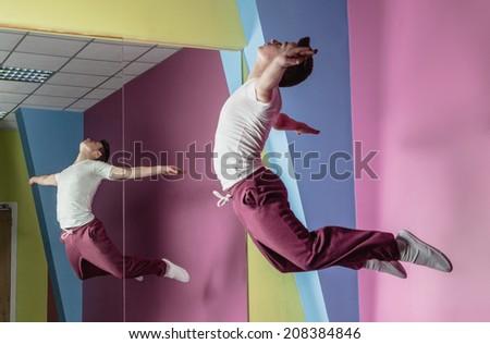 Cool break dancer mid air in front of mirror in the dance studio - stock photo