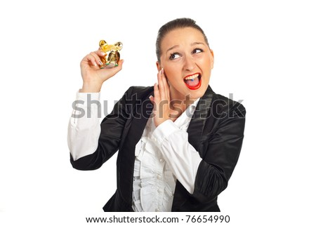 Cool business woman trying to hear the piggy bank sound isolated on white background