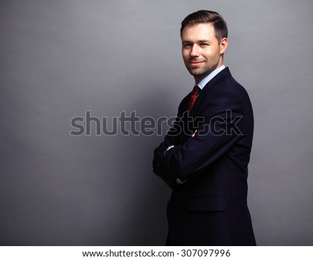Cool businessman standing on grey background  - stock photo