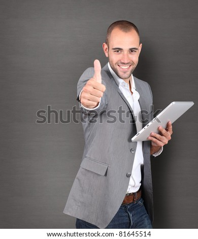 Cool businessman using touchpad on grey background - stock photo