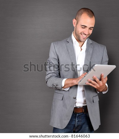 Cool businessman using touchpad on grey background