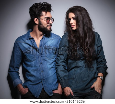 cool casual couple looking at each other in studio - stock photo