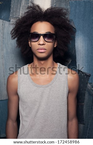 Cool casual. Young African man in sunglasses standing against jeans background - stock photo