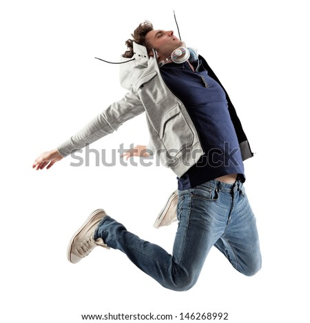 Cool Caucasian man with headphones around his neck jumping. - stock photo