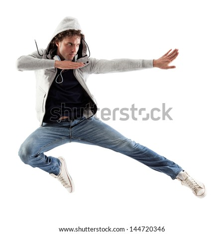 Cool Caucasian man with headphones around his neck jumping in a karate-like  way.
