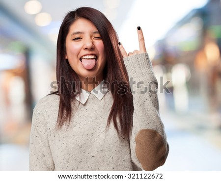 cool chinese-woman rock-gesture - stock photo