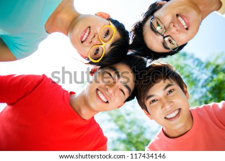 Cool classmates standing head to head and smiling, concept of unity and team-spirit - stock photo