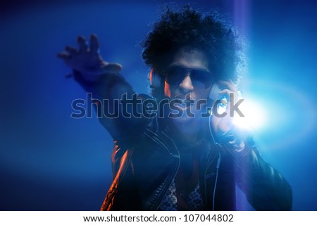 Cool club DJ gets the party started while listening to headphones and dancing in nightclub with afro and lens flare