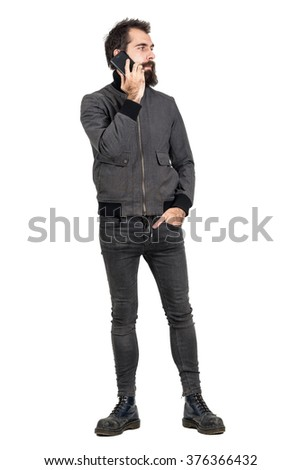 Cool confident serious hipster wearing gray jacket and military boots talking on the cellphone looking away. Full body length portrait isolated over white studio background.