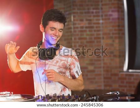 Cool dj spinning the decks at the nightclub - stock photo