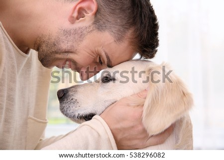 Cool dog and young man having fun at home