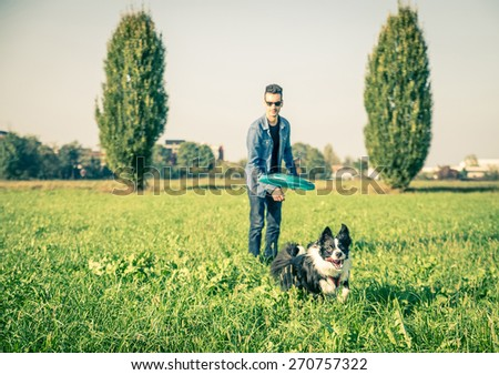 Cool dog and young man having fun with frisbee in a park - Australian shepherd dog running  and trying to catch a frisbee - Concepts of friendship,pets,togetherness.Focus on frisbee - stock photo