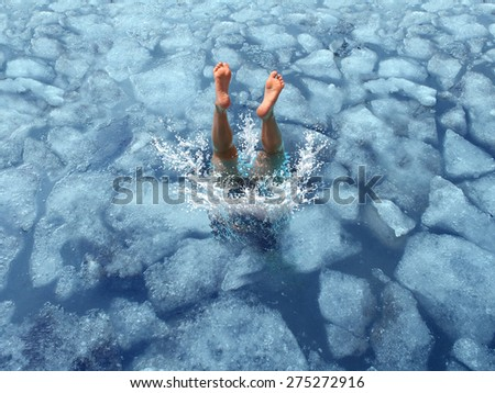 Cool down and Cooling off concept as a diver diving into frozen ice water as a symbol for managing hot weather summer heat and refreshing break from a heatwave. - stock photo
