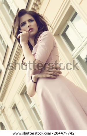 cool fashion portrait of beautiful brunette girl with trendy pink dress, natural hair-style and stylish make-up. she has an old bulding as background - stock photo