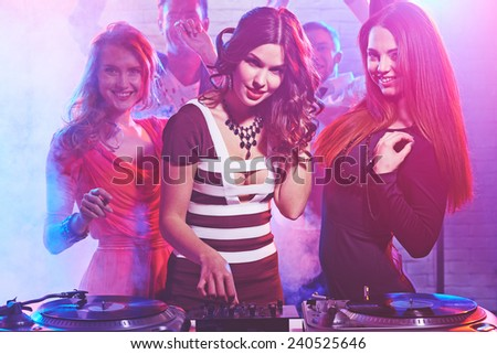 Cool girl by deejay equipment and company of friends - stock photo