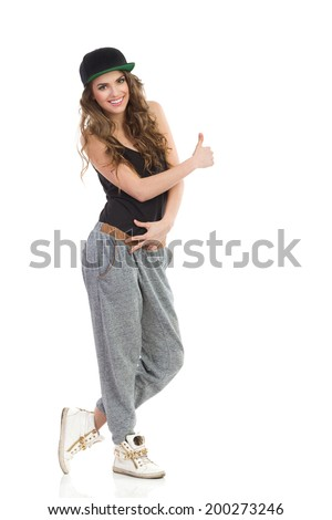 Cool girl giving thumb up. Smiling young woman in gray track-suit, black top and full cap showing thumb up. Full length studio shot isolated on white.