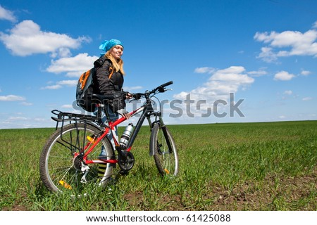 Cool girl riding a bicycle in the countryside, with blue sky and clouds.