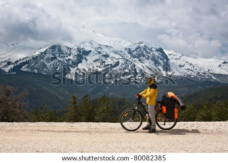 Cool girl traveling by bicycle in the countryside, with big high mountain in clouds.