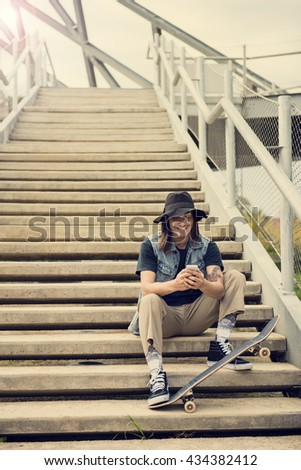 Cool guy in the city writing a message on his smart phone - stock photo