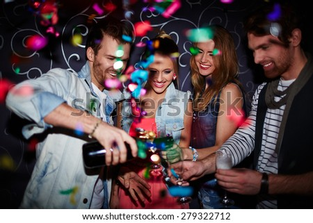 Cool guy pouring champagne in flutes of his friends