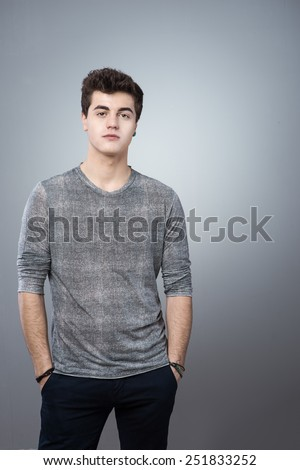 Cool guy standing with hands in pockets against gray background