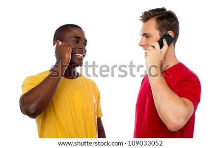 Cool guys communicating via cellphone, looking at each other. All on white background