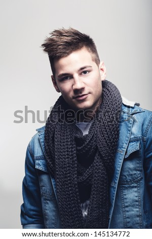 Cool handsome young teenage boy with a slick modern hairstyle in a trendy scarf and jacket looking at the camera
