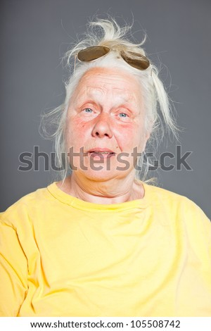 Cool hip senior woman with sunglasses and long grey hair. Expressive face. Studio shot isolated on grey. - stock photo