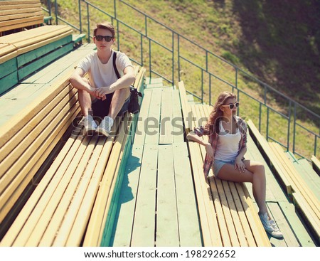Cool hipster couple resting on the bench, youth, teenagers, fashion - concept - stock photo