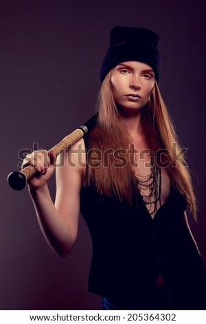 Cool hot fashionable woman bandit dressed in hat with baseball bat