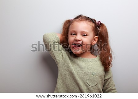 Cool kid girl showing the tongue with funny face on grey background - stock photo