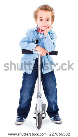Cool little boy in jeans standing on his scooter - stock photo
