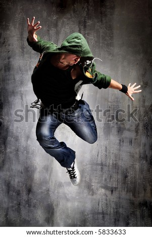 cool looking dancer posing on a grunge grey wall - stock photo