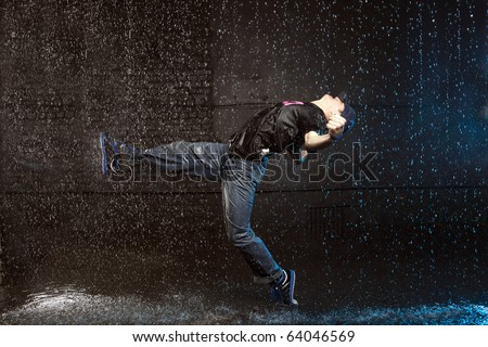 Cool looking hip-hop dancer in aqua studio - stock photo