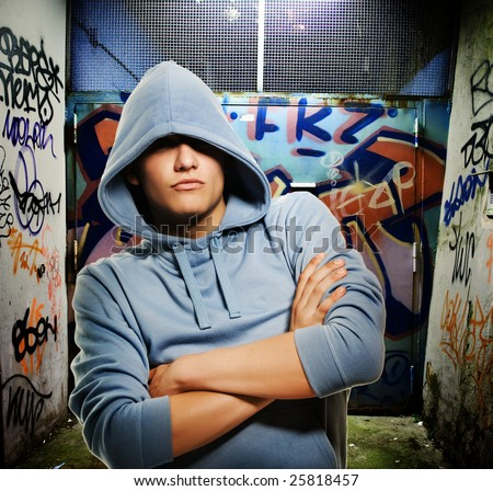 Cool looking hooligan in a graffiti painted gateway - stock photo