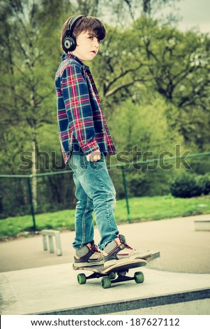 cool looking skater boy with headphone, vintage effect added - stock photo