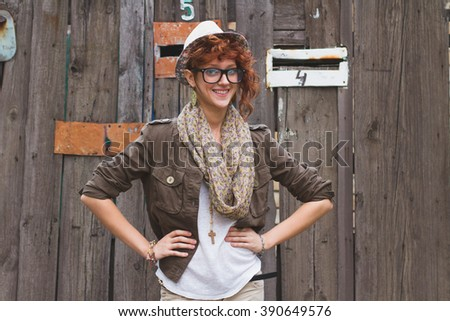 Cool looking young hipster girl in glasses and hat on wooden background. - stock photo