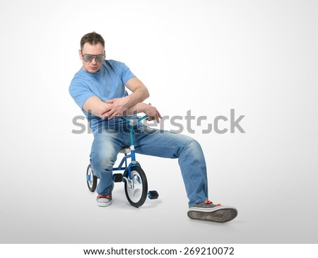 Cool man in a glamor glasses on children's bicycle - stock photo