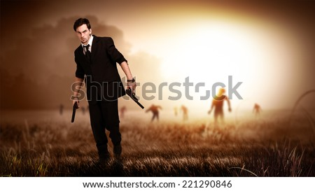 cool man in a suit holding guns, standing on a field with many zombies behind him - stock photo