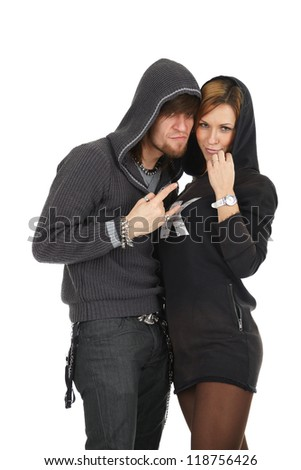 Cool modern young couple in hoods looking with conspiracy