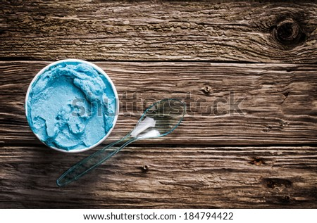 Cool refreshing blue Italian ice cream in a takeaway tub with a plastic spoon for a welcome treat on a hot summer day served on an old wooden table with copyspace, view from above - stock photo