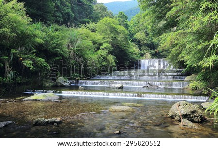 Cool refreshing cascades hidden in a mysterious forest of lush greenery~ Fresh cascade in a mysterious forest with sunlight through the lavish greenery ~ Scenery of Taiwan - stock photo