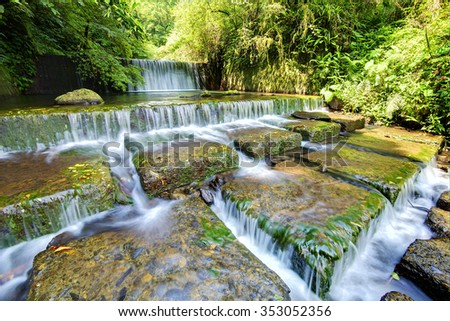 Cool refreshing cascades of a stream hidden in a mysterious forest of lush greenery ~ Beautiful river scenery of Taiwan in springtime - stock photo