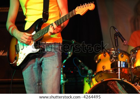 Cool rocker playing guitar in  a rock concert - stock photo