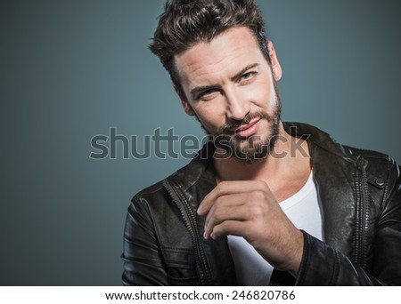 Cool seductive man in black leather jacket flirting and looking at camera